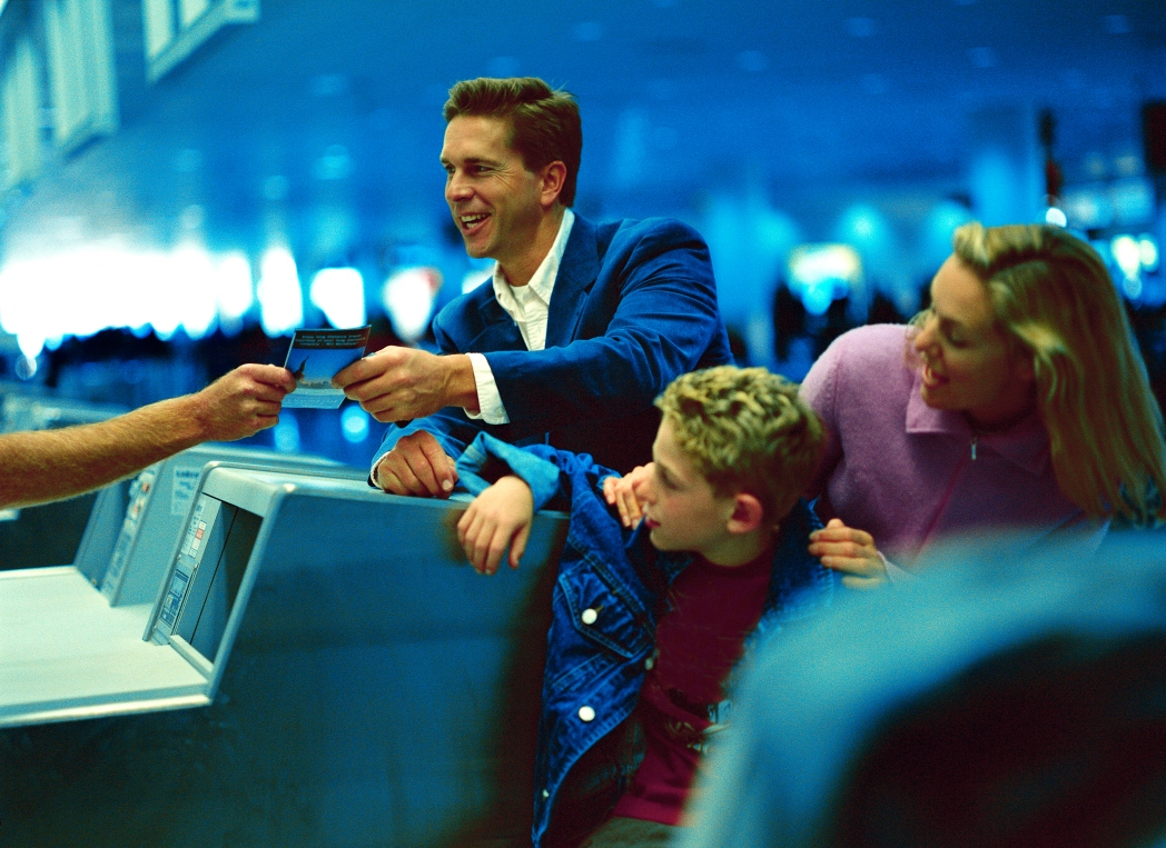 Smiling man at check-in counter at airport with wife and son standing to the side