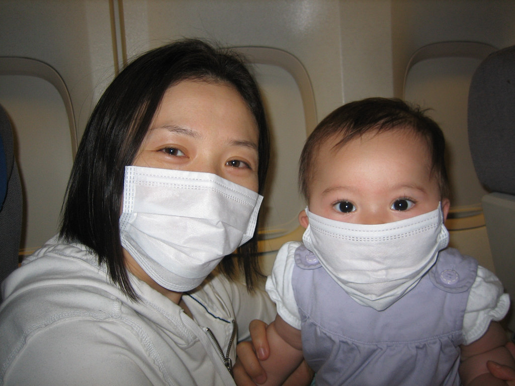 Mother and child wearing face masks on plane