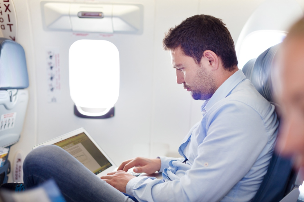 Man sitting with lots of room on a plane working on his laptop