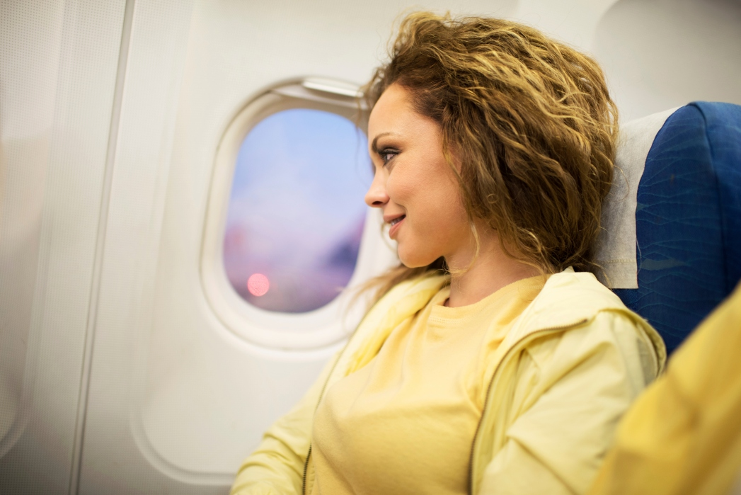 A woman in a yellow dress looks out a plane window